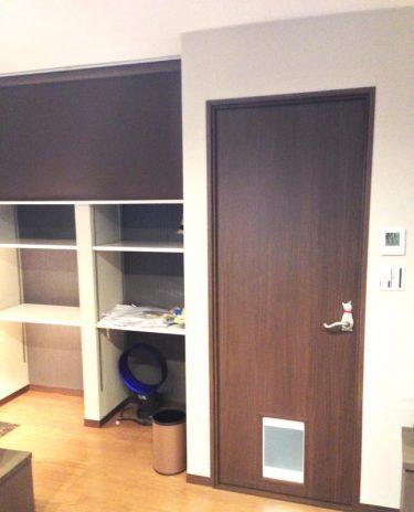"""和室には必ずある床の間スペースは、ロールスクリーンで仕切った収納に。<br /> ドアはネコ専用の入口がある""""猫ドア""""、さらにドアレバーは""""ネコのしっぽ""""!"""